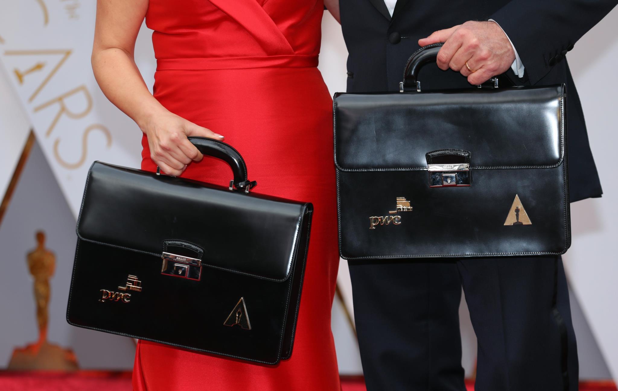 Martha Ruiz e Brian Cullinan na passadeira vermelha antes da cerimónia com as pastas em que transportavam os envelopes com os vencedores