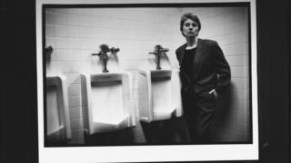 Camille Paglia a posar junto aos urinóis de uma casa de banho masculina, nos anos 90