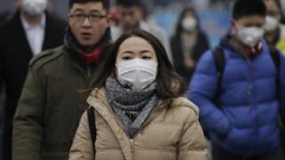"""Pedestres usam máscaras de protecção durante """"alerta vermelho"""" contra a poluição em 2015, em Pequim, China"""