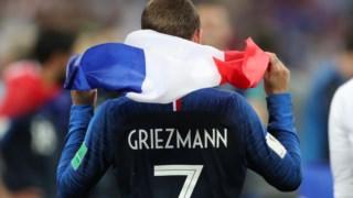 Griezmann no relvado com a bandeira de França, antes da conferência onde homenageou o Uruguai