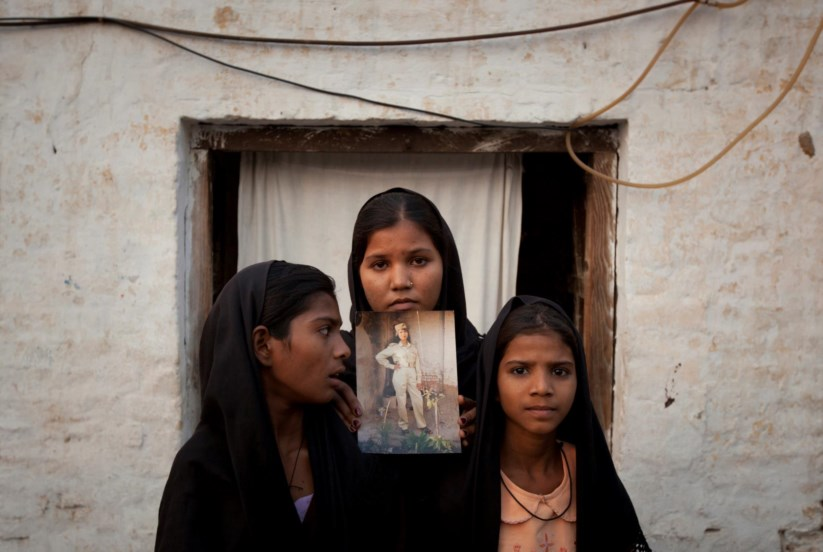 As filhas de Asia Bibi com uma fotografia da mãe