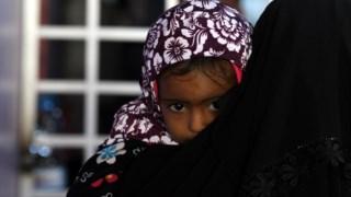 Uma mãe espera por cuidados médicos para a filha no Iémen