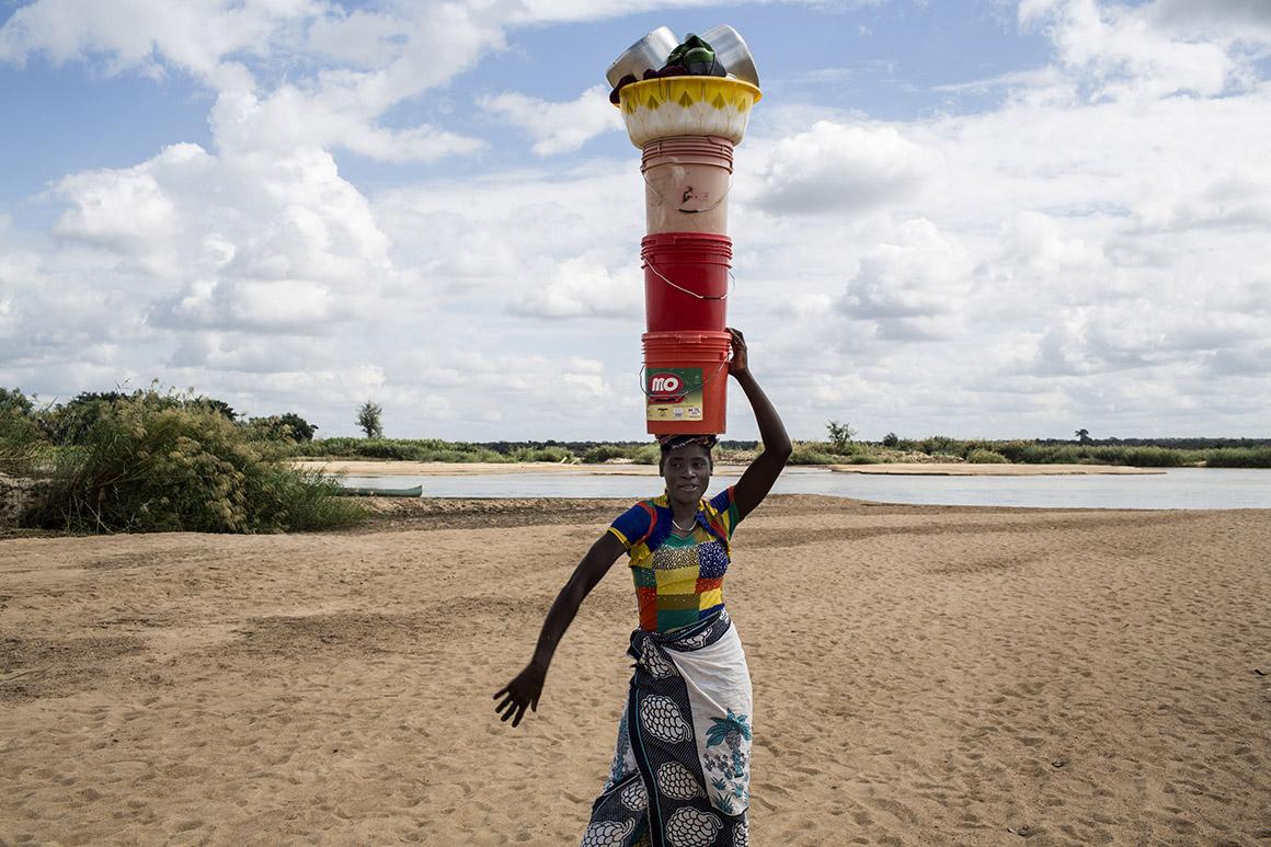 Mulher transporta na cabeça utensílios domésticos nas margens do rio Rovuma em Negomano, Cabo Delgado