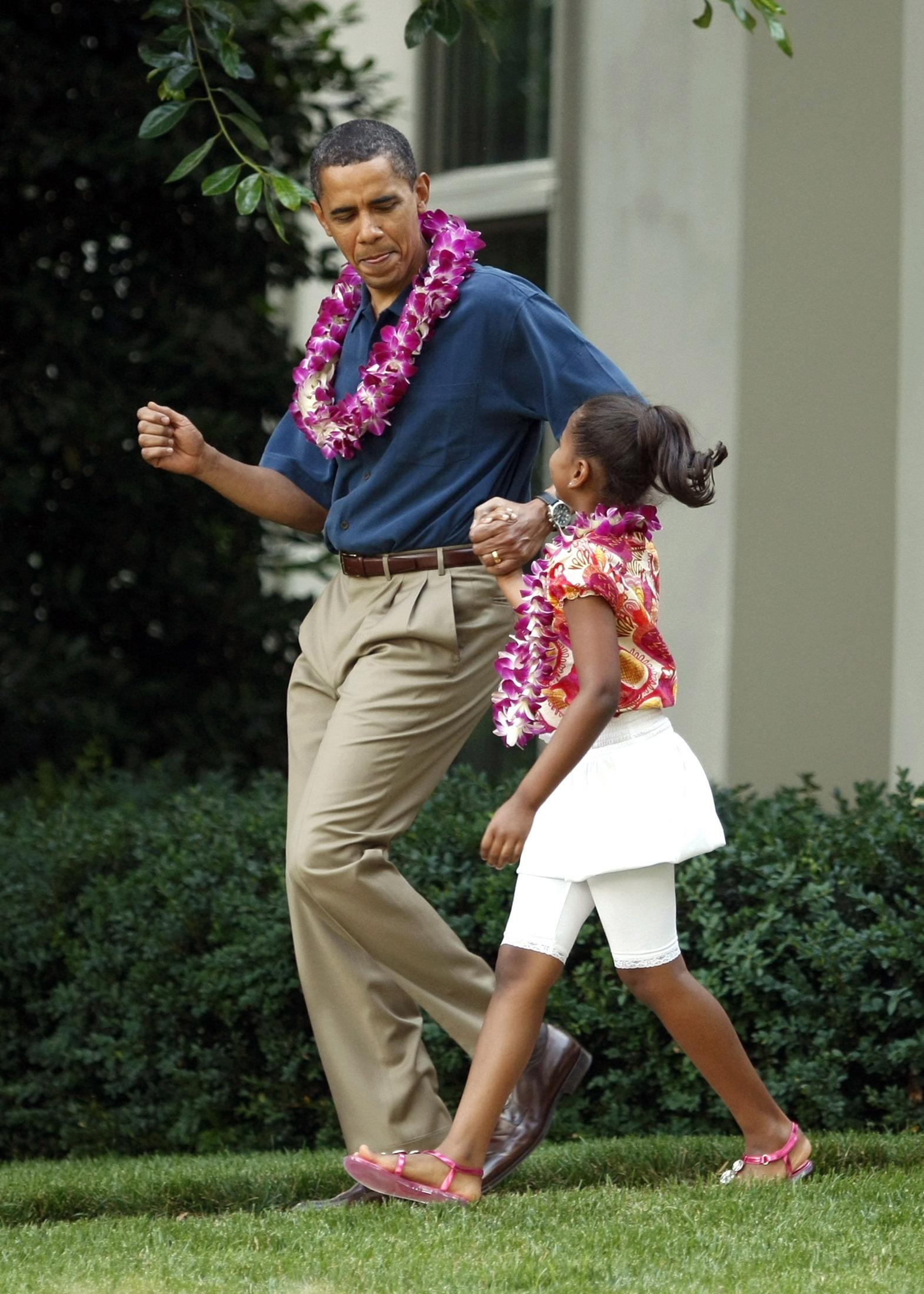 Barack Obama com a filha Sasha a caminho de uma festa havaiana em Washington, 2009