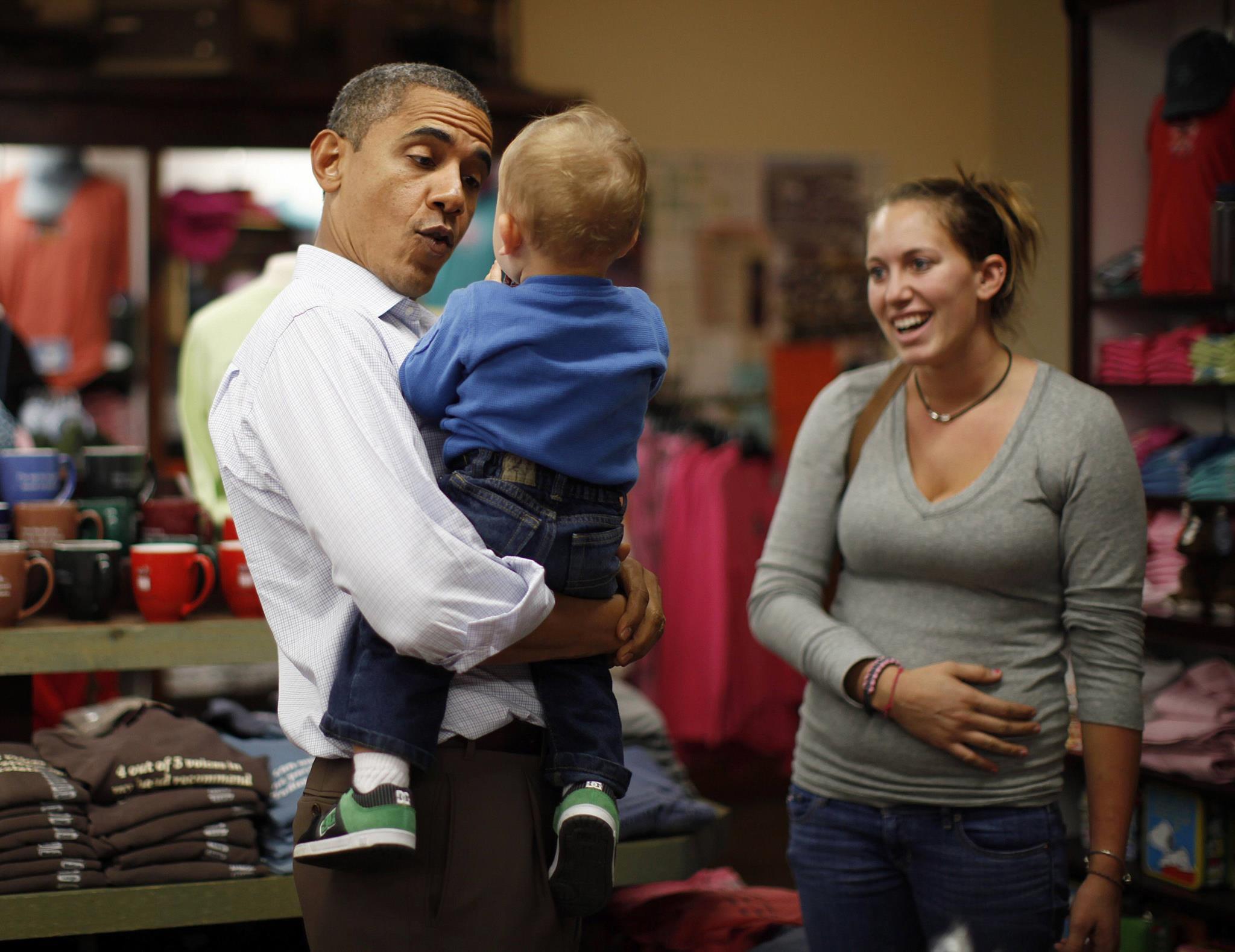 Obama cumprimenta uma criança de um ano de idade e sua mãe durante uma viagem de autocarro de três dias pela Carolina do Norte e Virgínia, para promover o projecto <i>American Jobs Act</i>, 2011
