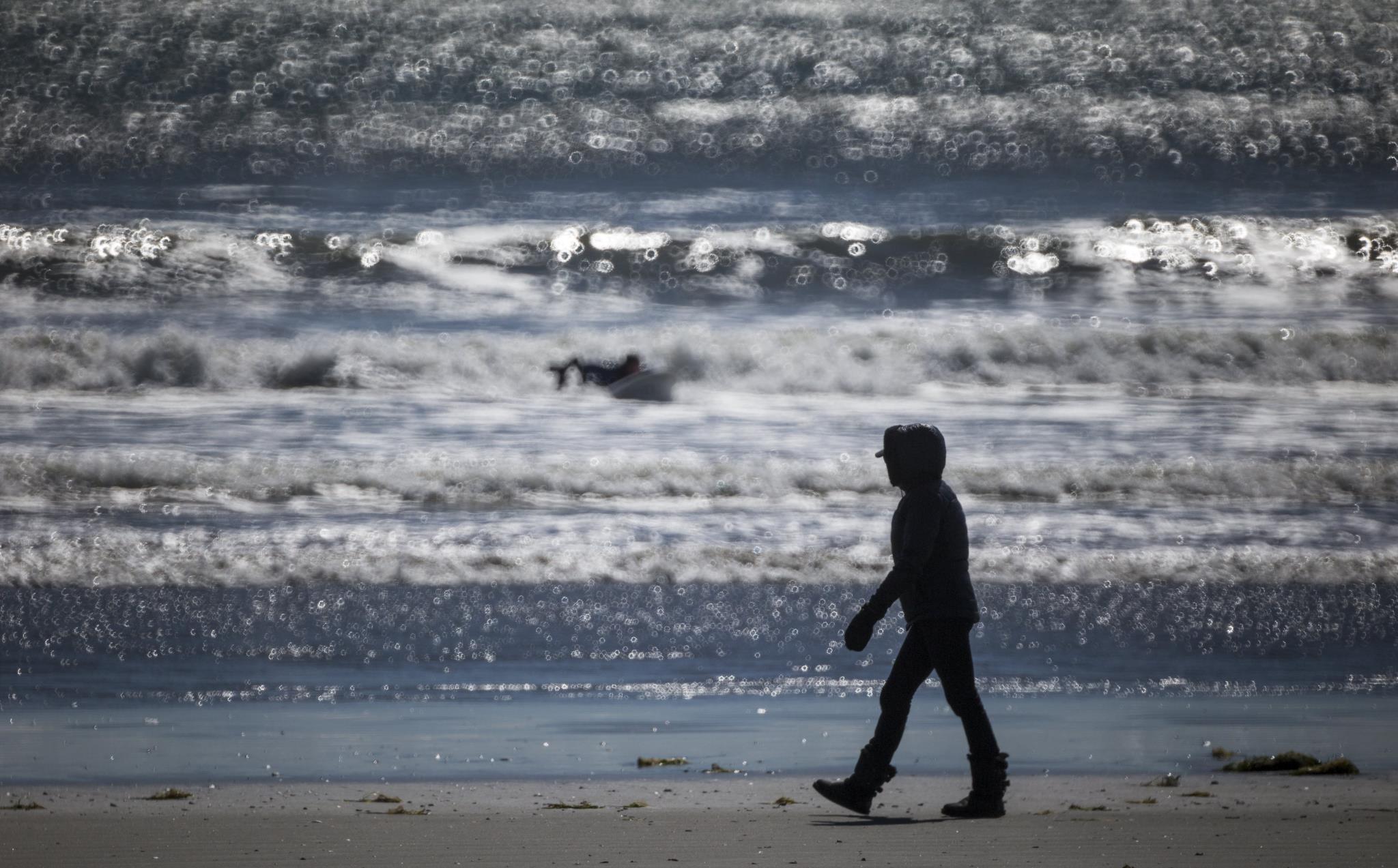 Uma mulher caminha numa praia no estado de Massachusetts, nos Estados Unidos, onde as temperaturas máximas rondaram os 10º