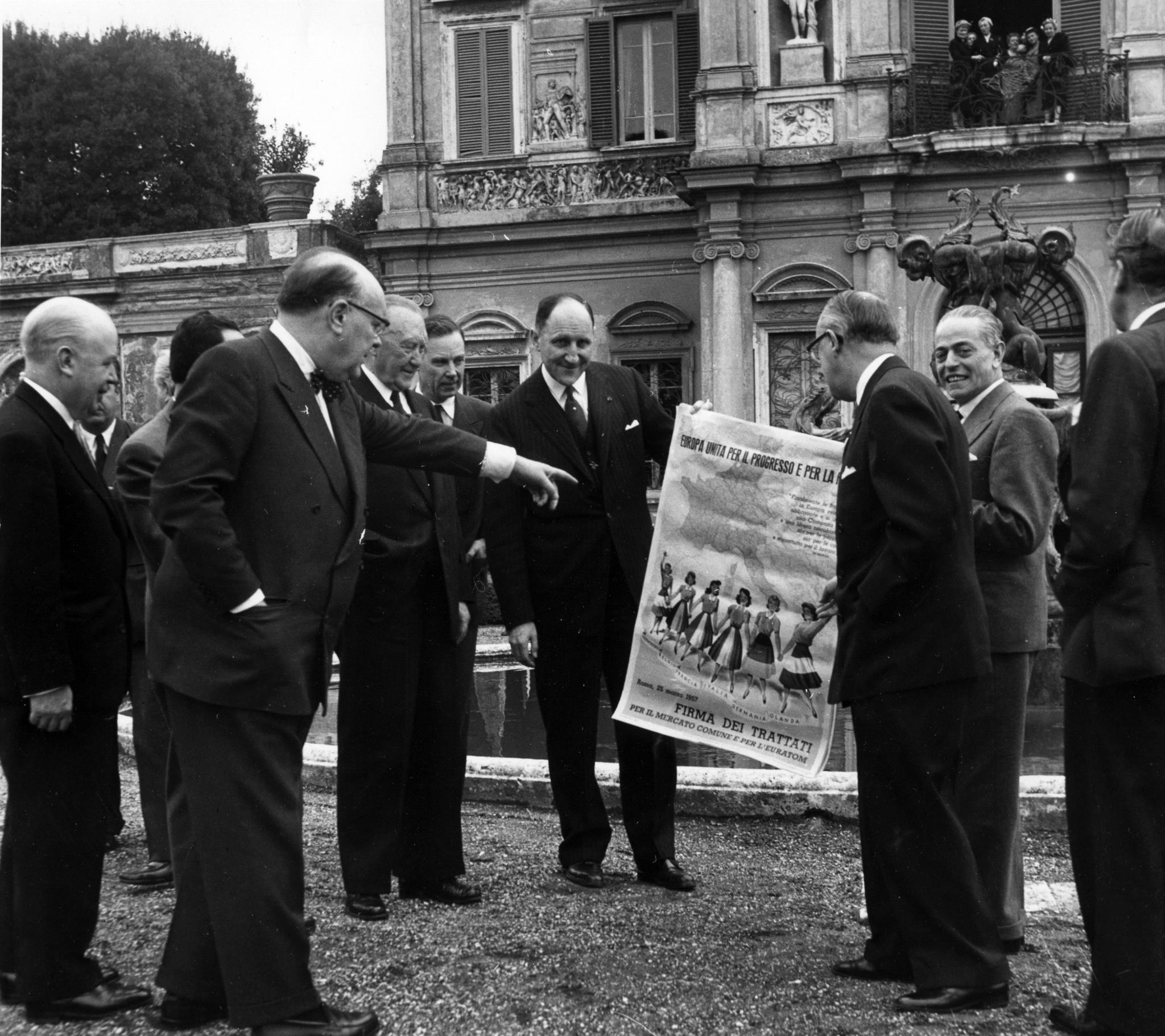 Signatários dos tratados reunidos no jardim da embaixada da Bélgica em Roma, observando um poster que assinalava o evento