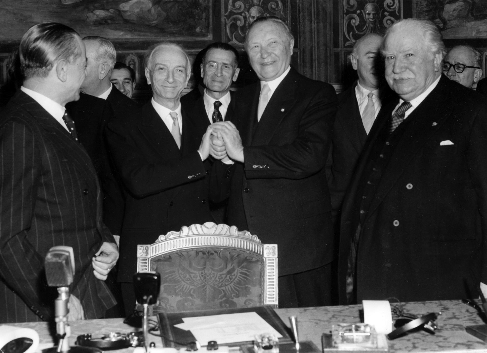 Ao centro, da esquerda para a direita: Antonio Segni e Konrad Adenauer, a apertar as mãos depois da assinatura dos tratados, rodeados por outros signatários e membros das delegações.