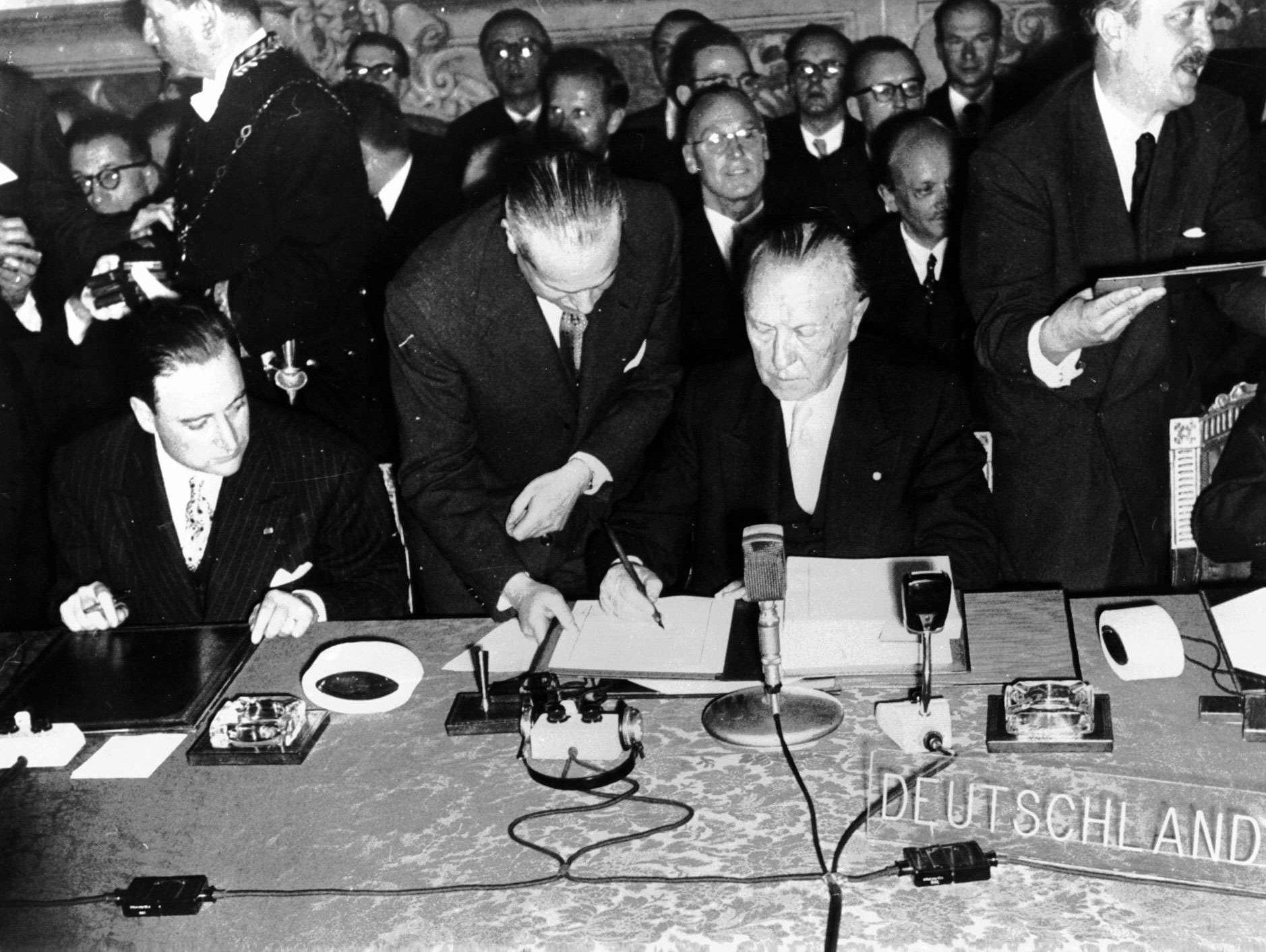 Konrad Adenauer, sentado à direita, a assinar os tratados em nome da Alemanha