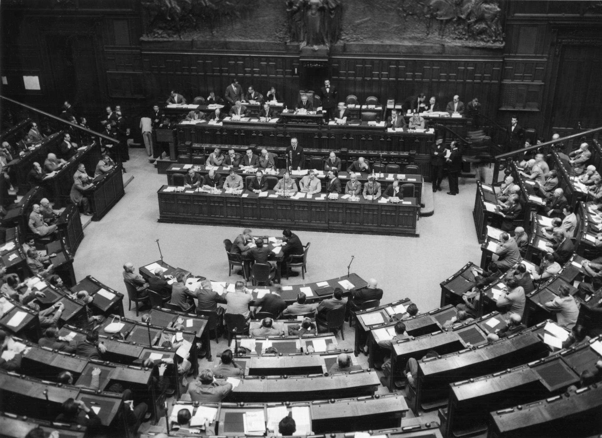 Antigo primeiro-ministro italiano Giuseppe Pella em pé, ao centro, a falar sobre o Euratom e o Mercado Comum na câmara dos deputados em Roma, a 28 de Julho de 1957