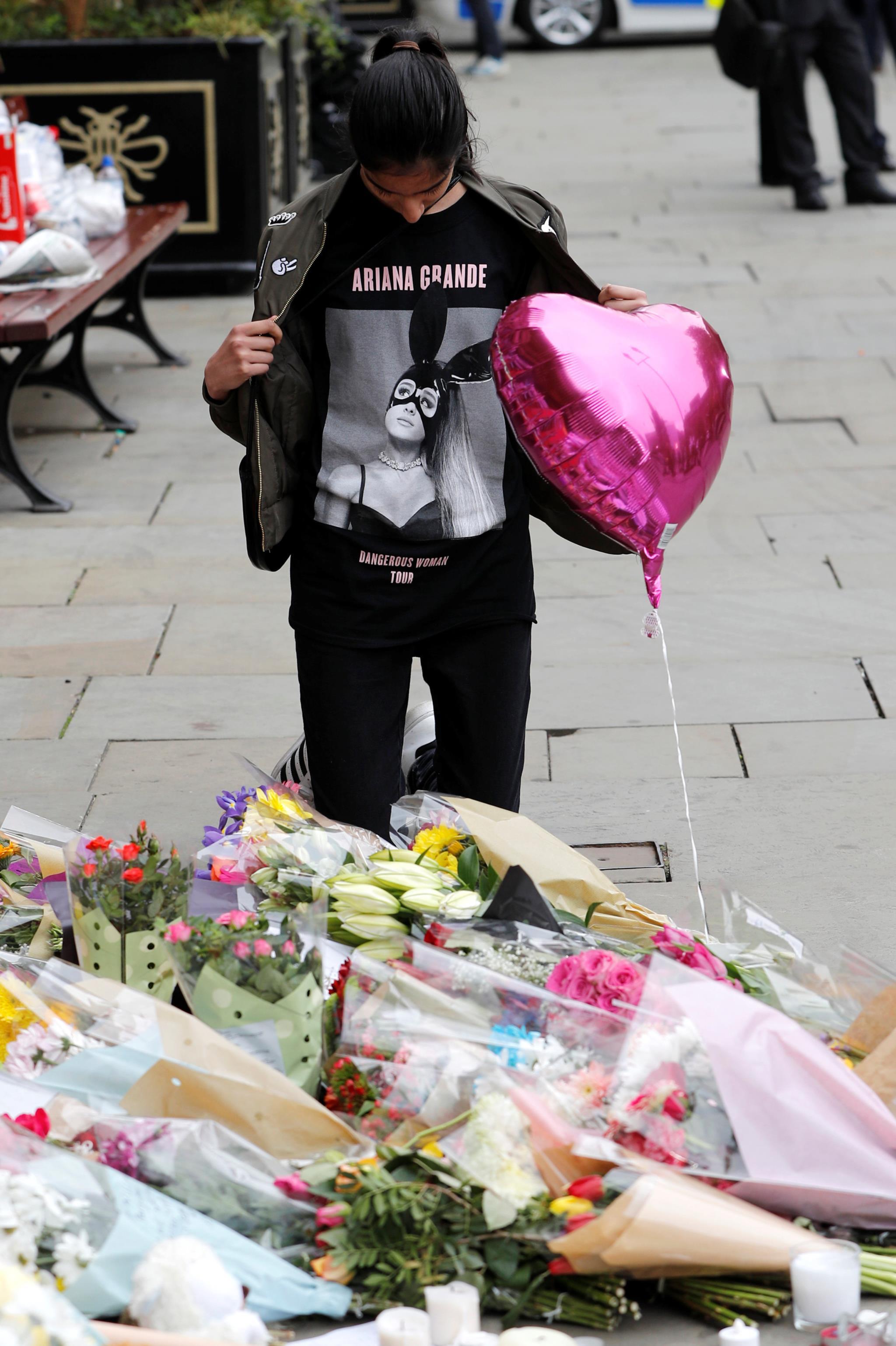 Uma fã de Ariana Grande num memorial com flores pelas vítimas do atentado que aconteceu no final do concerto da cantora, em Manchester