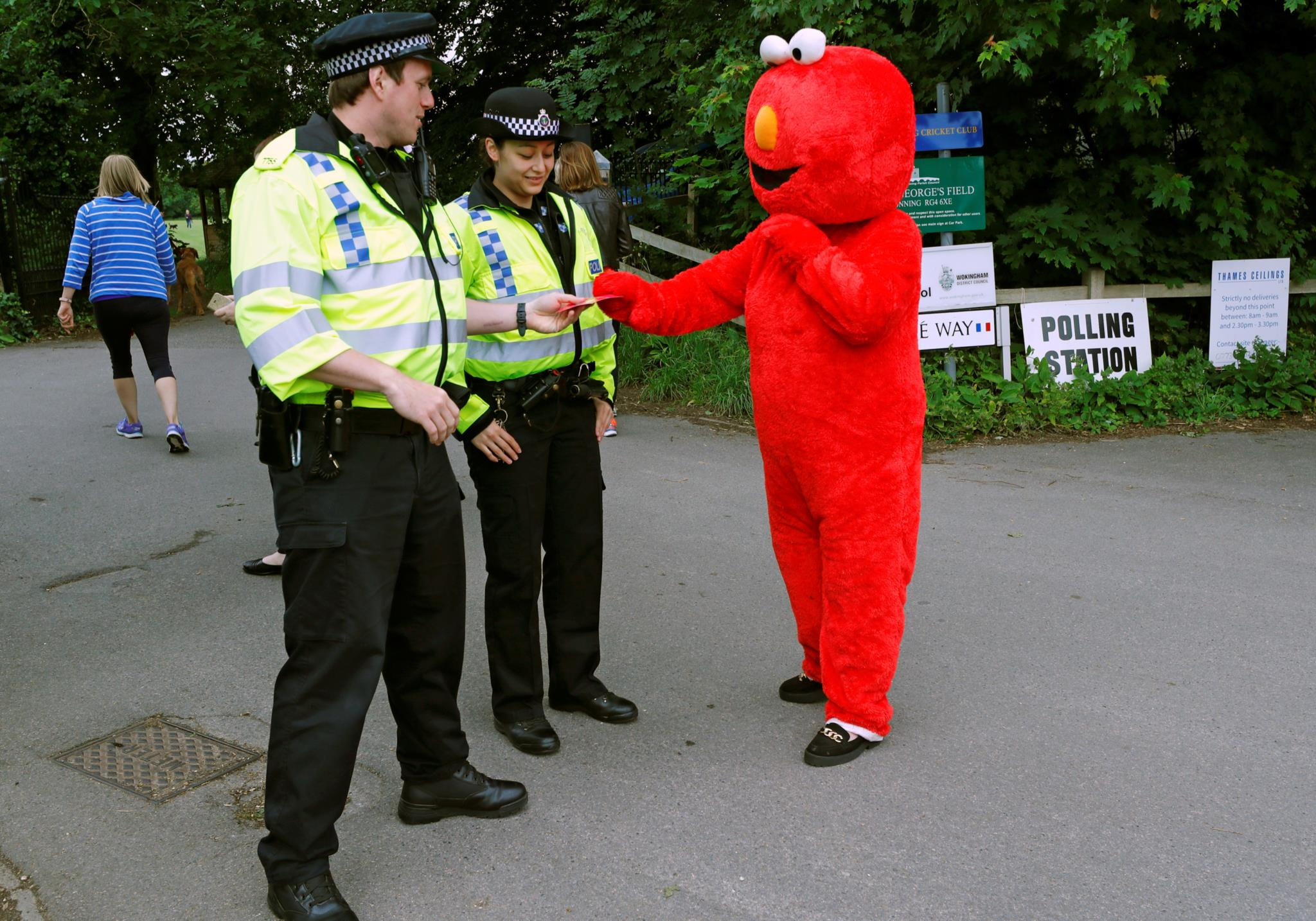 """Agentes da polícia conversam com um homem disfarçado de um popular personagem da """"Rua Sésamo"""""""