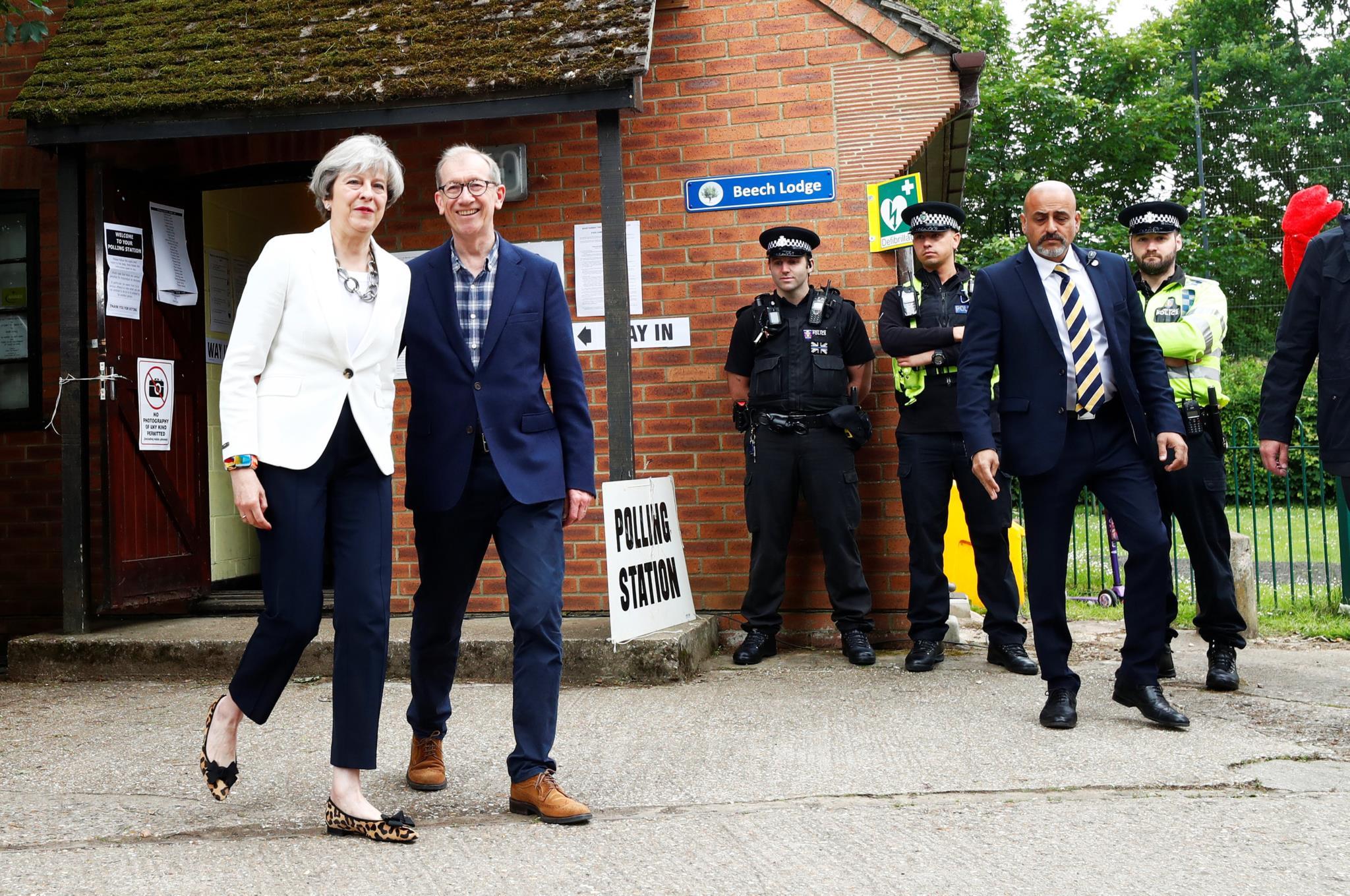 A primeira-ministra britânica, Theresa May, depois de votar, em Sonning, nesta quinta-feira, acompanhada pelo marido