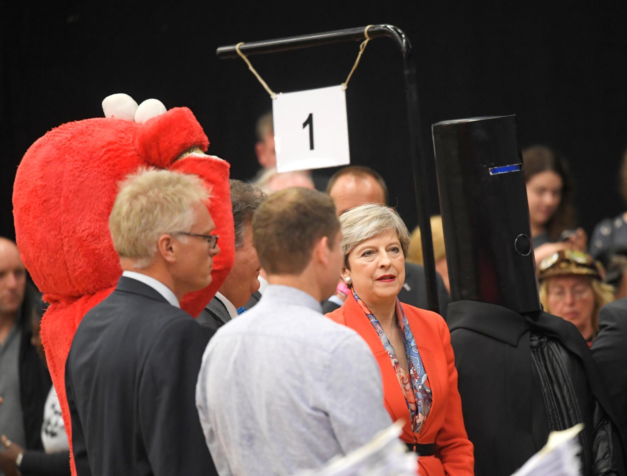 Theresa May rodeado por um candidato vestido de Elmo e pelo Lord Buckethead (Lorde Cabeça de Balde)