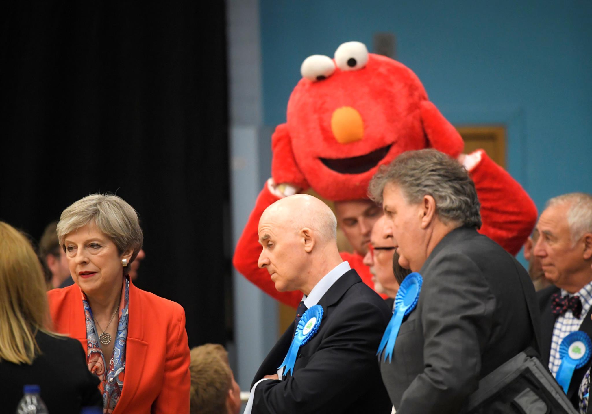 Theresa May rodeado por um candidato vestido de Elmo