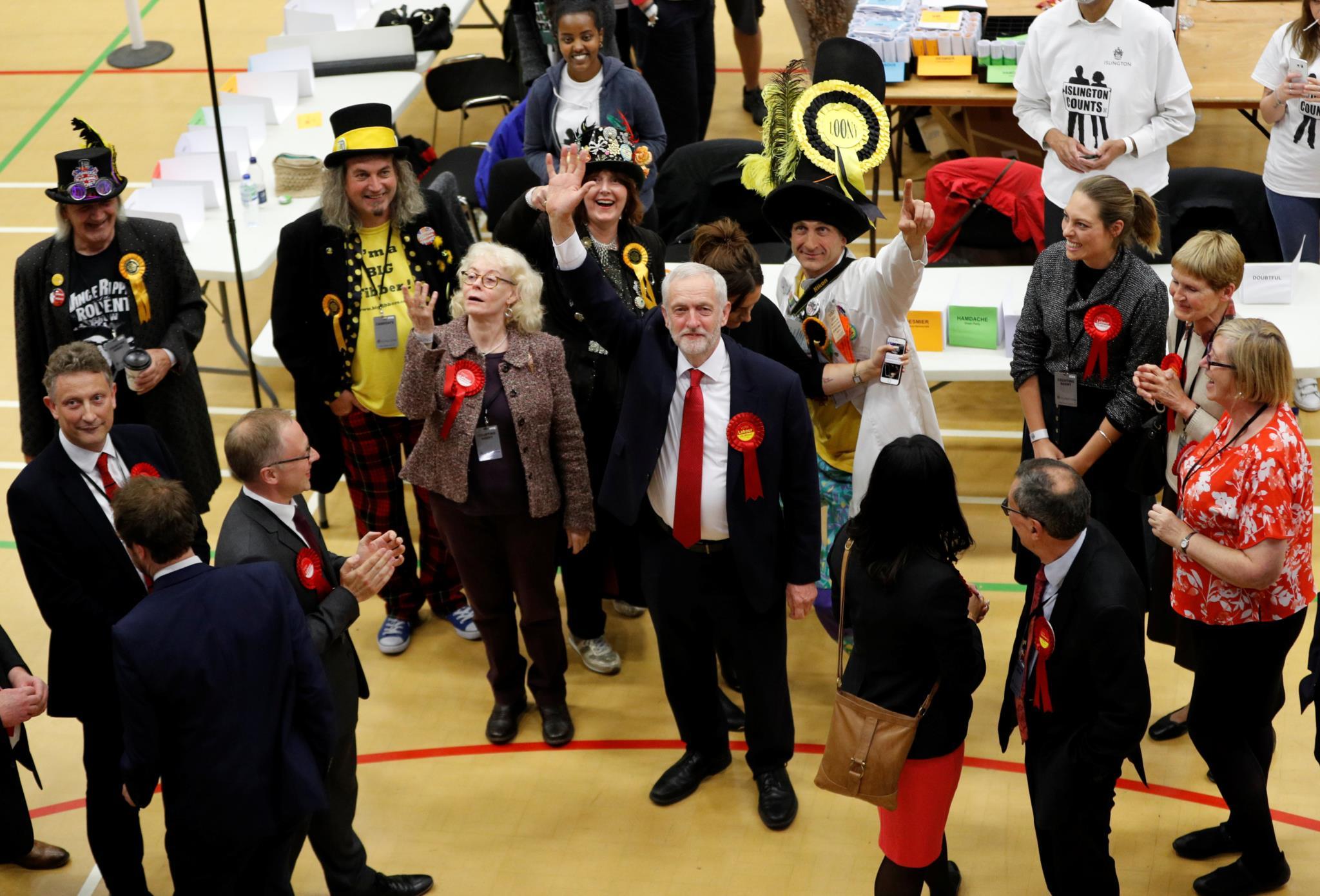 Jeremy Corbyn à chegada a um centro de contagem de votos rodeado por candidatos do partido Official Monster Raving Loony Party