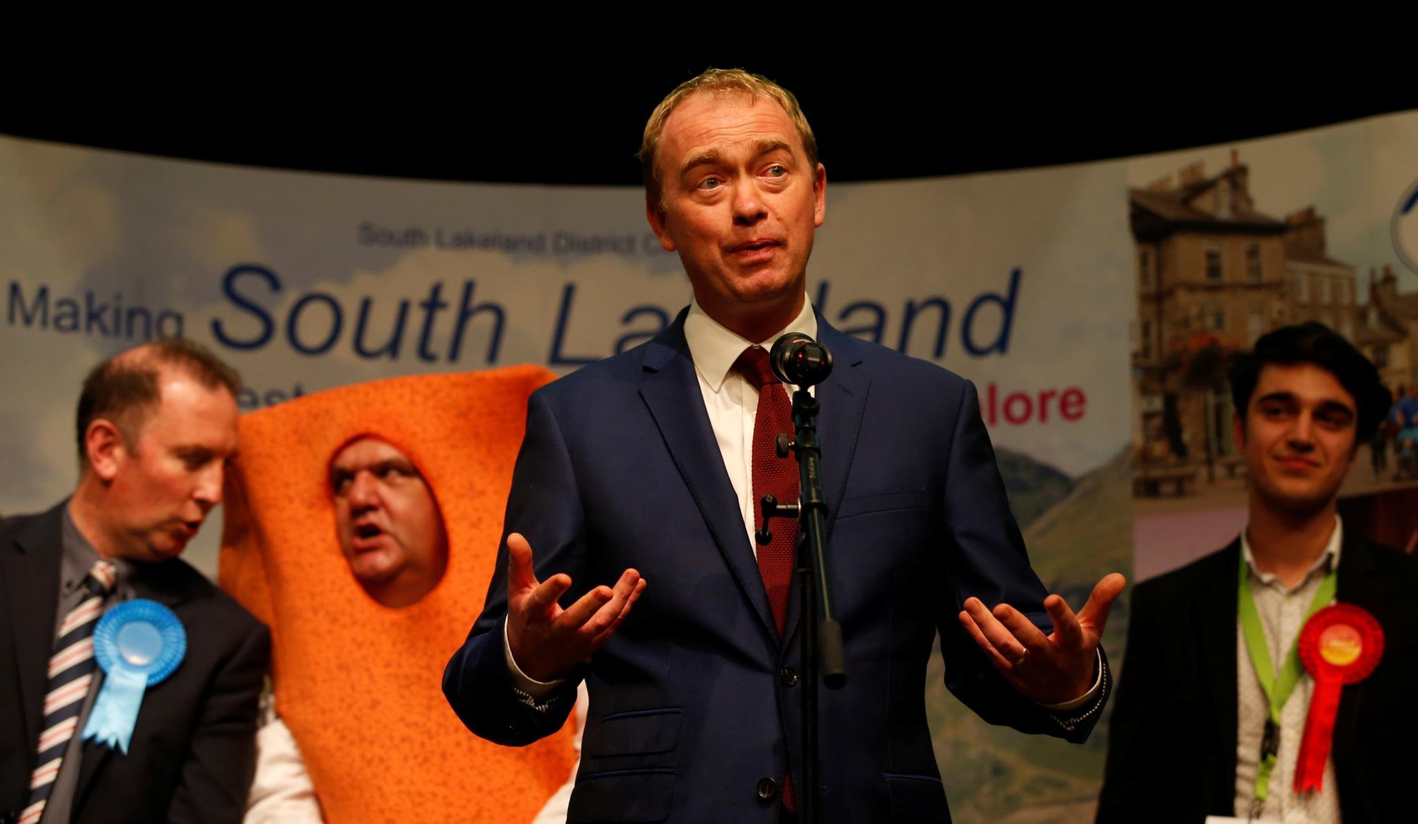 Tim Farron, líder dos liberais-democratas, discursa à frente do candidato Mr. Fishfinger (Sr. Douradinho, numa tradução possível)