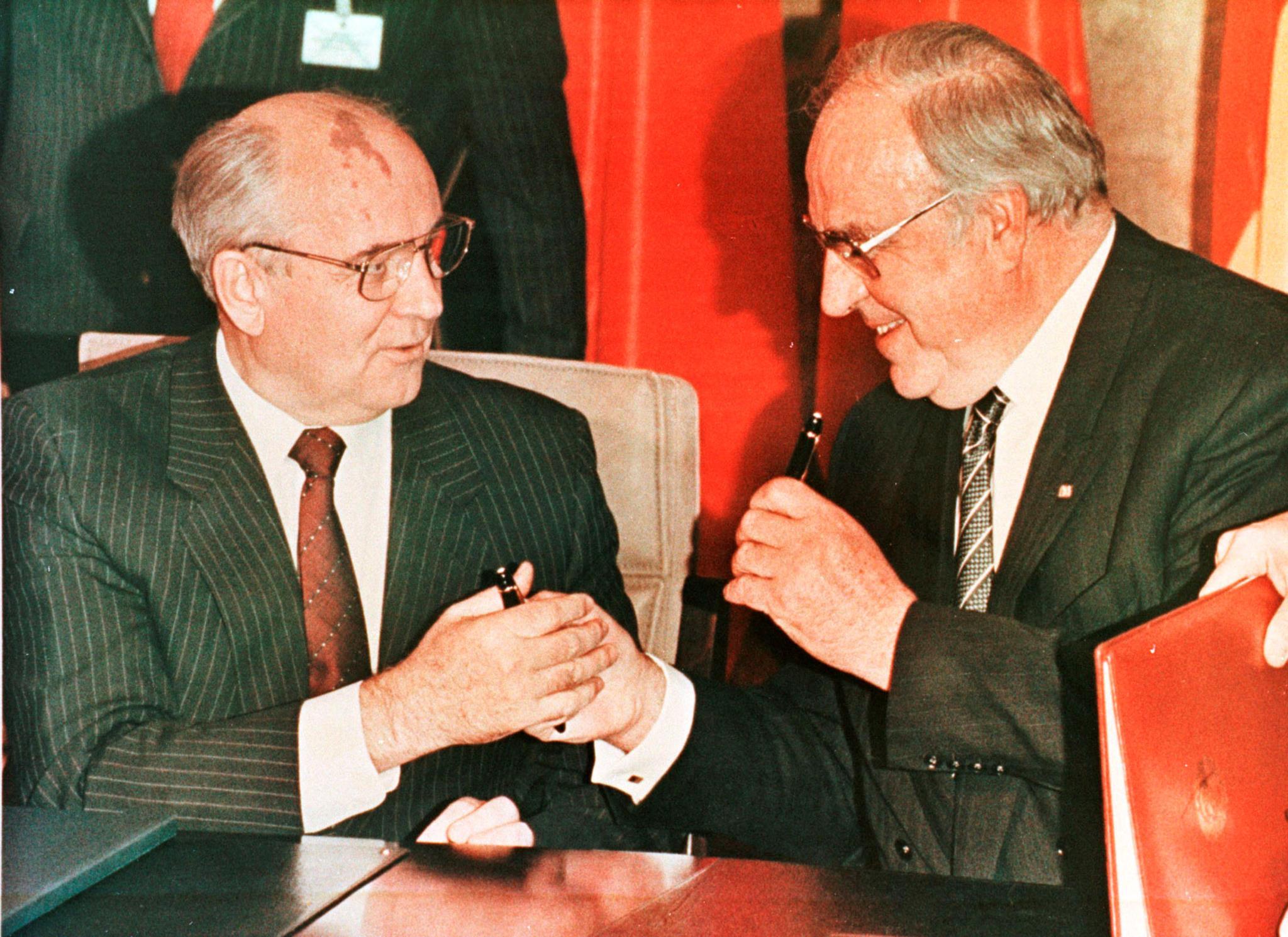 O líder soviético Mikhail Gorbachev e Helmut Kohl trocam canetas após assinarem um contrato em Bona,1990