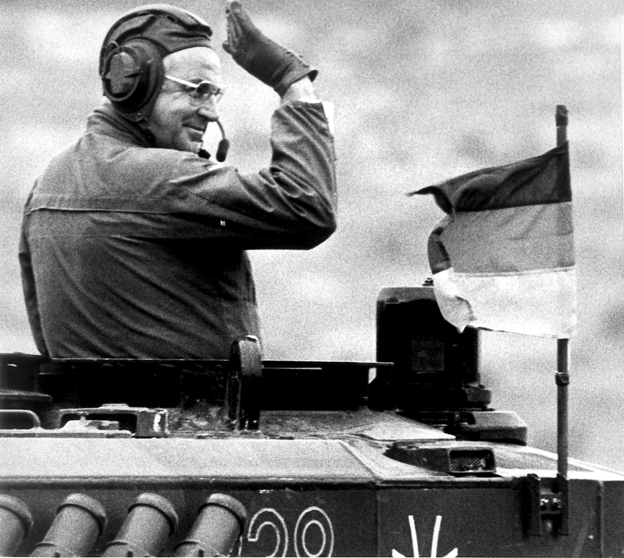 O chanceler alemão Helmut Kohl acena de um tanque durante uma visita às tropas alemãs e britânicas no norte da Alemanha, em 1986