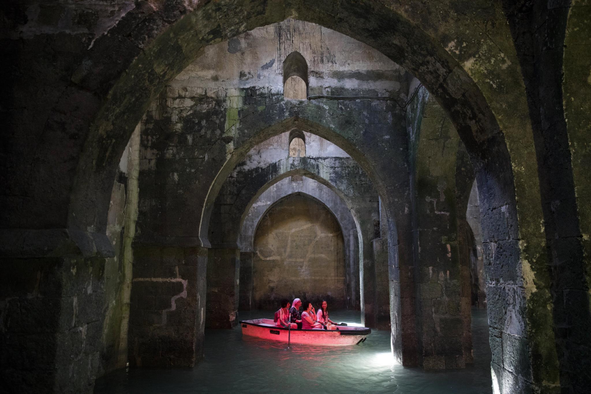 Turistas em pequenos barcos na piscina dos Arcos em Ramla, Israel, construída em 789 AD