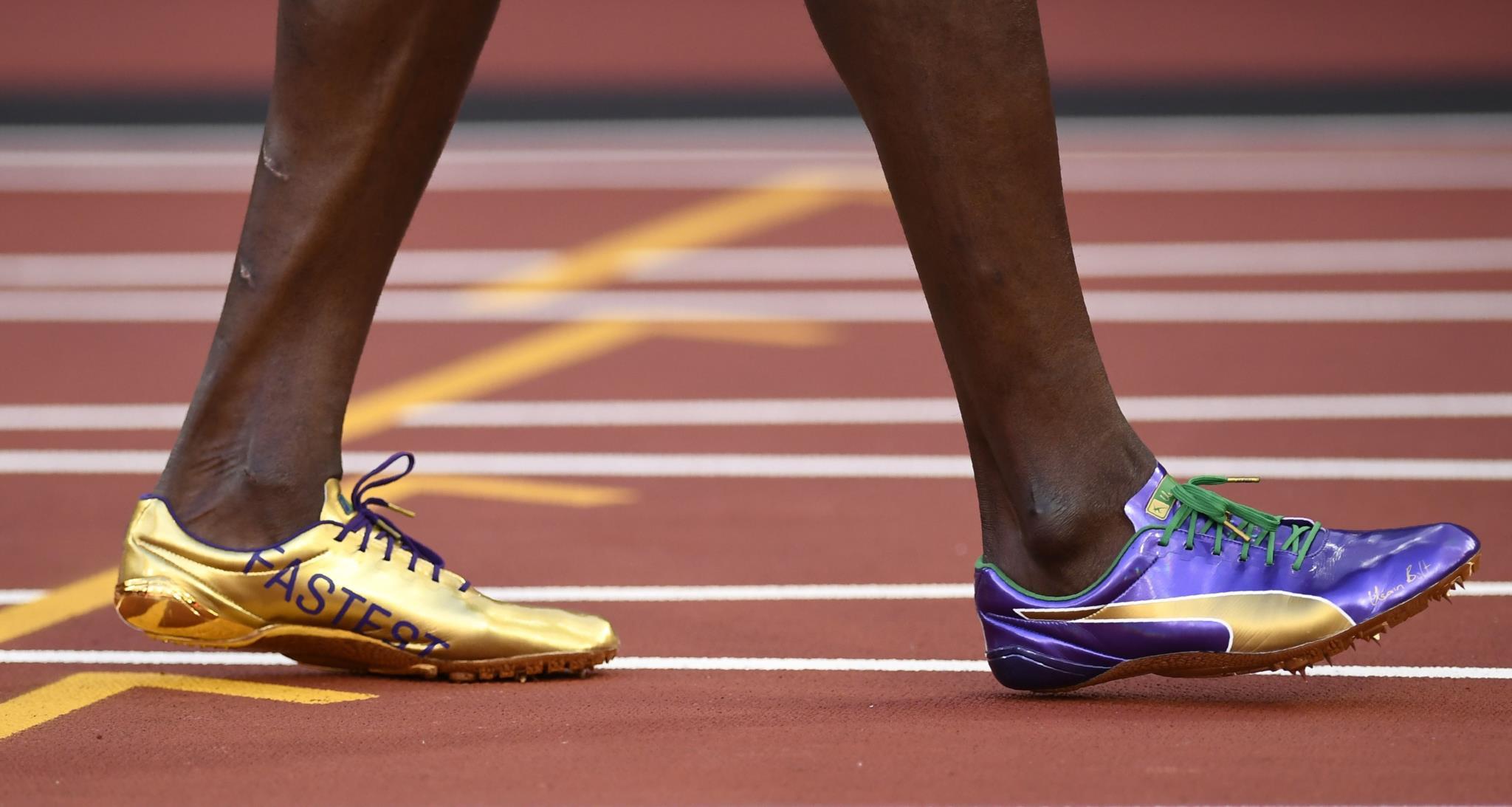 """Os sapatos de corrida de Bolt onde se pode ler """"mais rápido""""."""