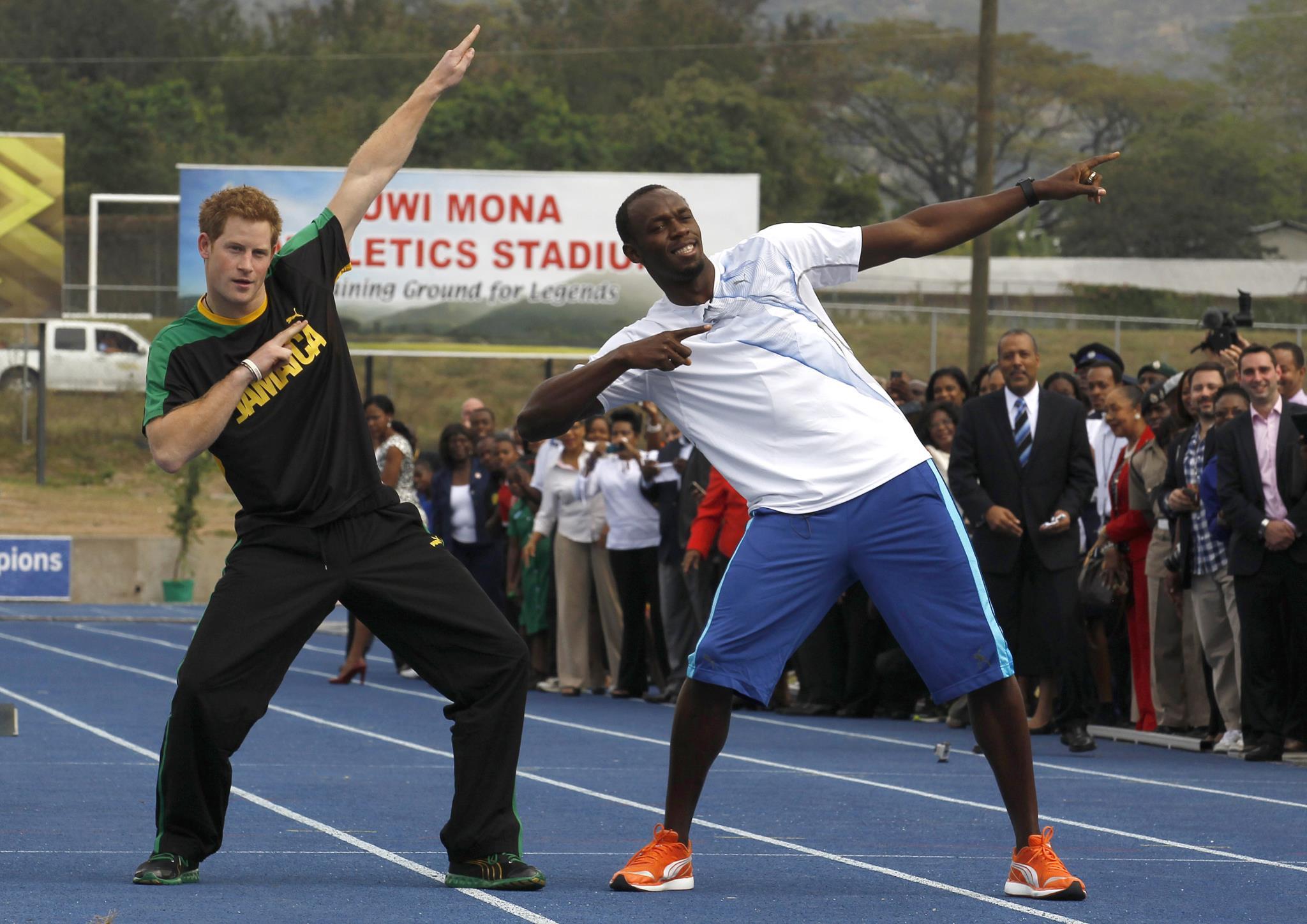 O príncipe Harry de Inglaterra com Usain Bolt, replicando o gesto icónico do atleta jamaicano.