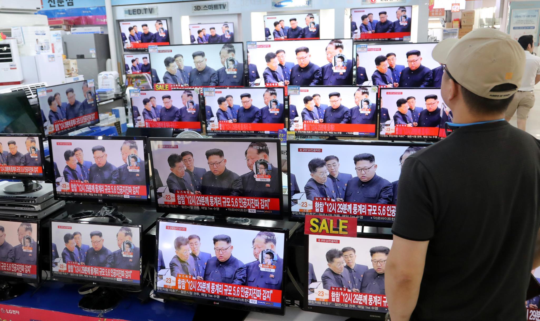 Um homem observa vários televisores numa loja de electrodomésticos em Seul, na Coreia do Sul