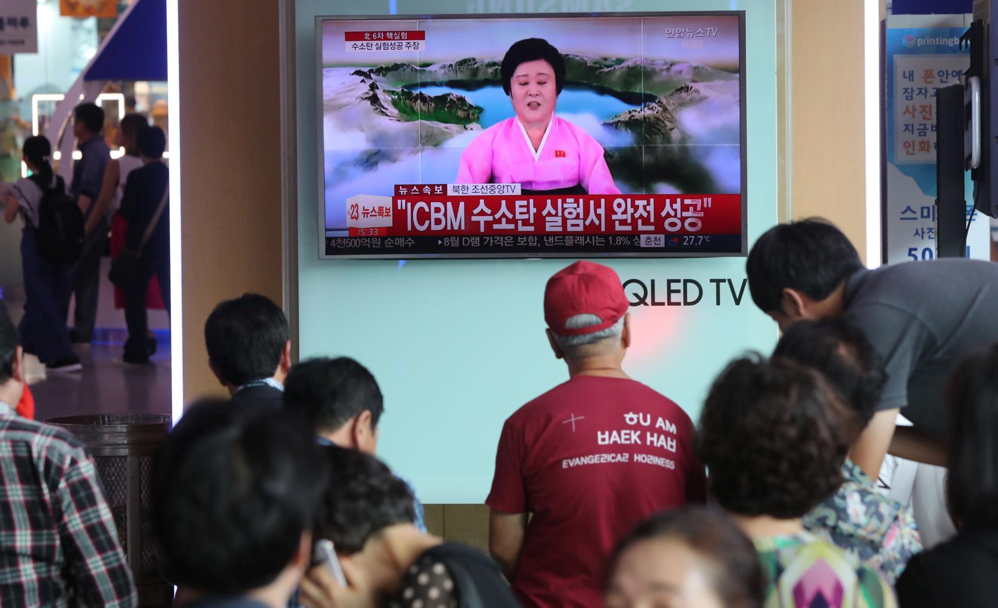 Sul-coreanos vêem as notícias numa estação de comboios em Seul