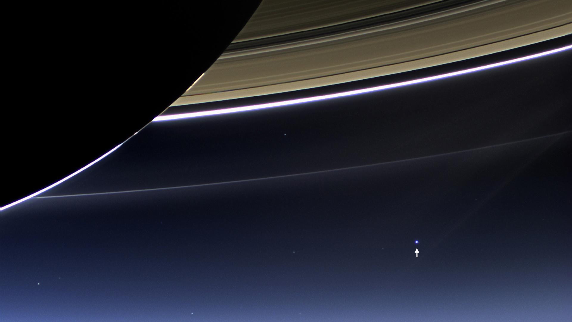Em primeiro plano, Saturno e os seu anéis. Ao longe, assinalada por uma seta, a Terra. A imagem foi obtida pela Cassini, a 19 de Julho de 2013, e ganha especial relevo na semana em que a sonda mergulha no planeta gigante e nós despedimos-nos dela