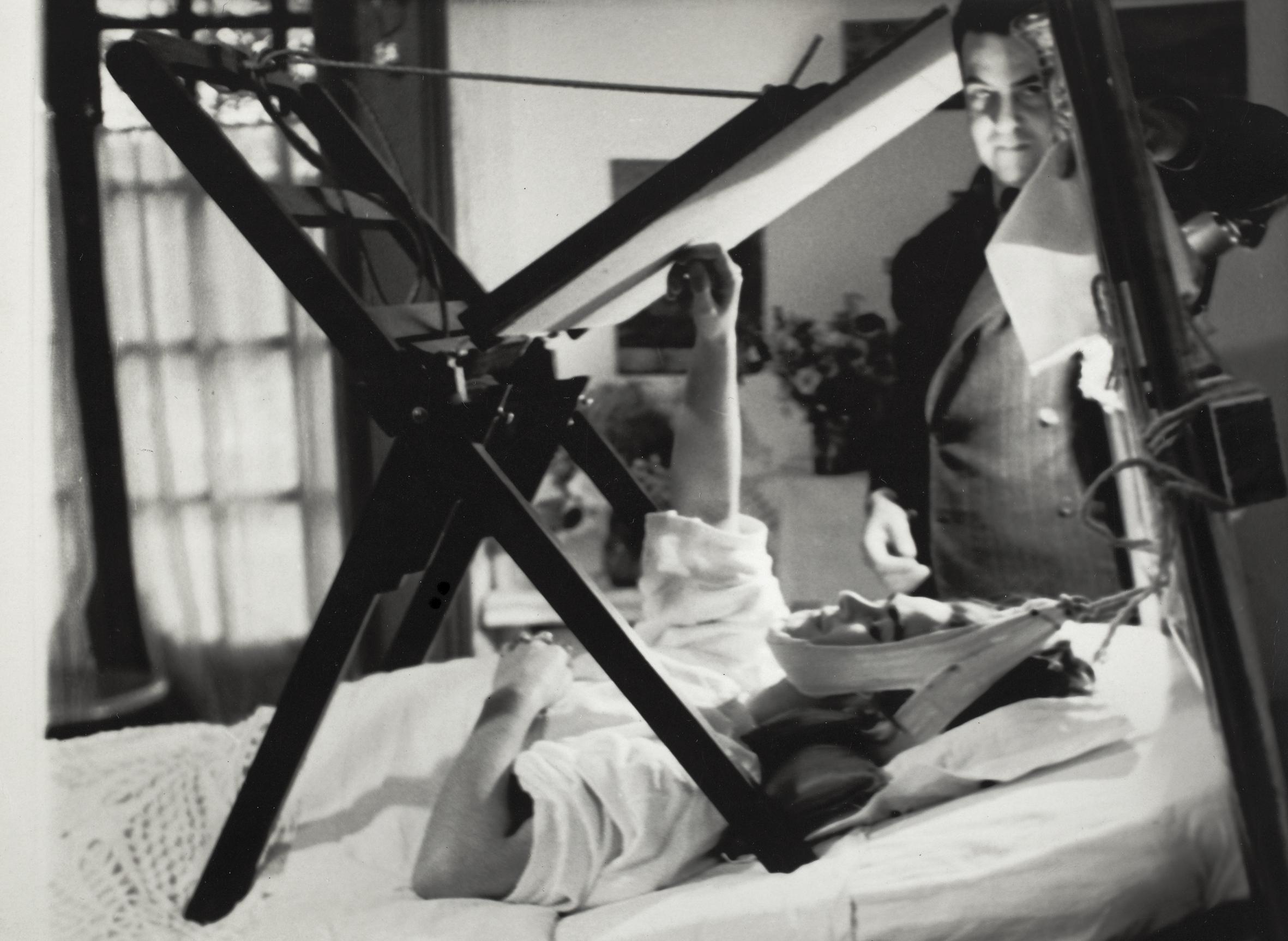Frida  pintando  na  sua  cama,  Anónimo,  1940.  De  pé,  ao  seu  lado,  Miguel  Covarrubias  ©  Museu  Frida  Kahlo