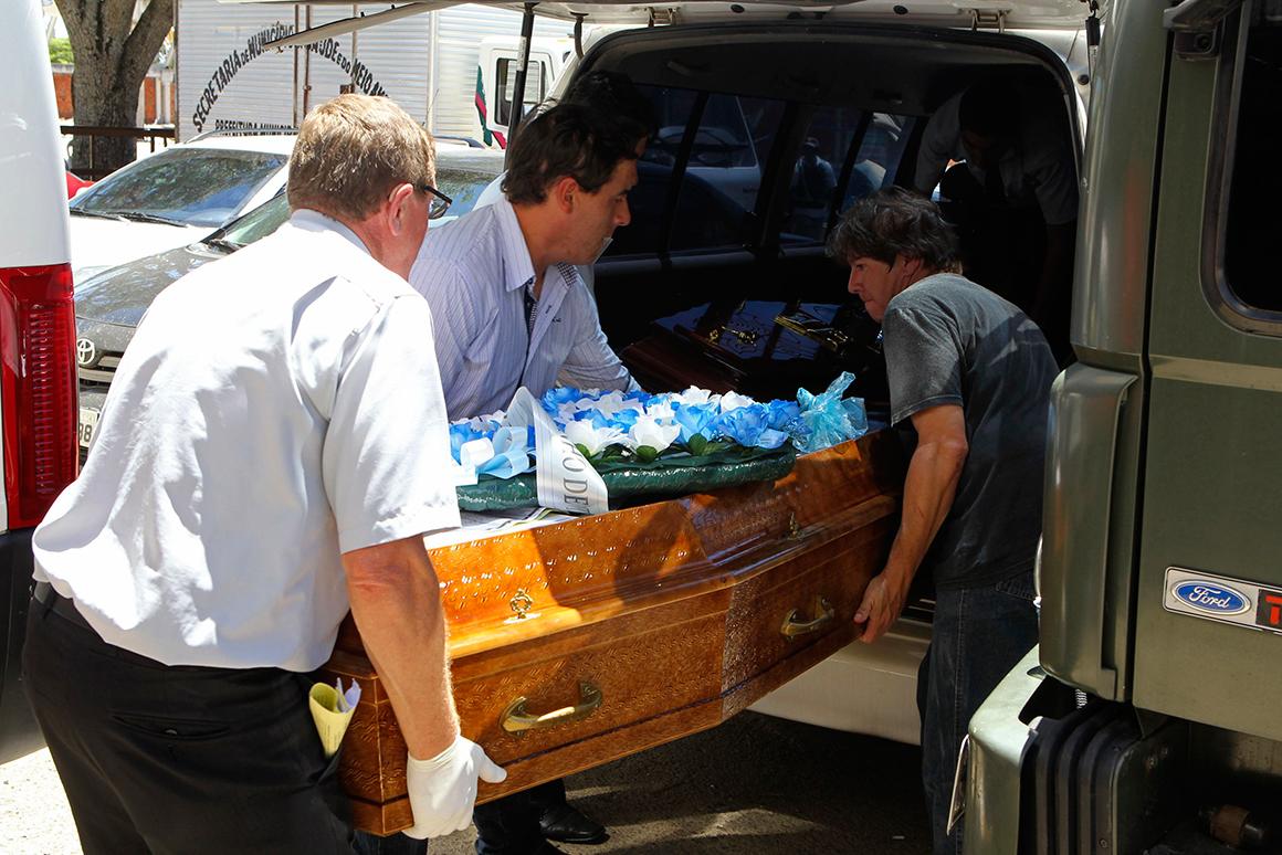 Trabalhadores de uma funerária transportam uma das muitas vítimas mortais
