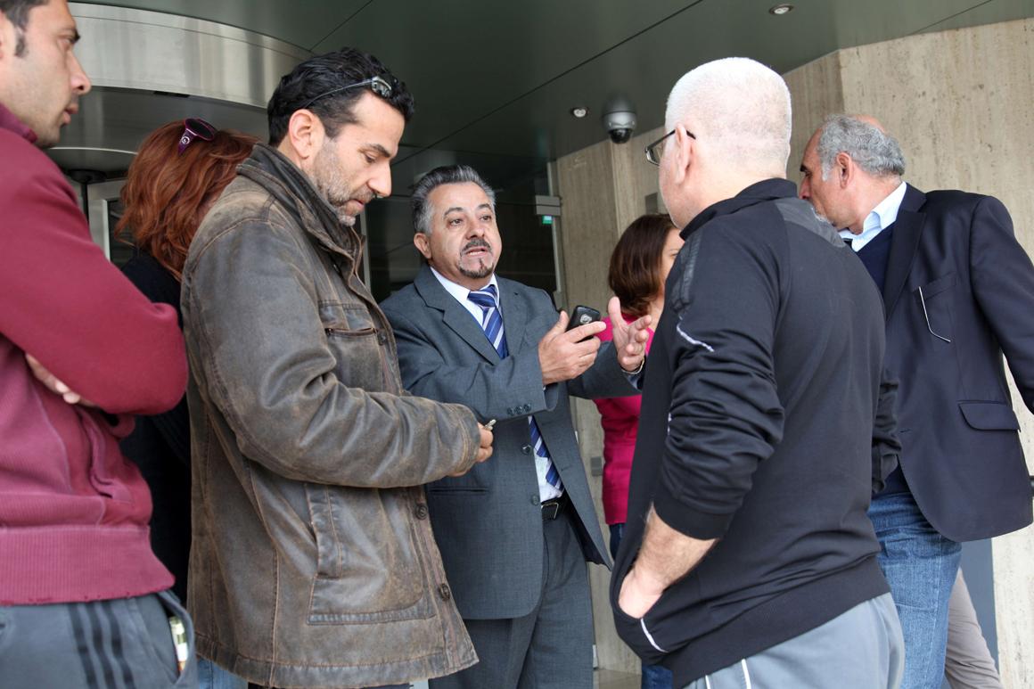 Cipriotas conversam com representante de um banco em Nicósia